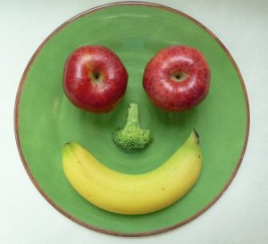 fruit shaped as a smiley face on a plate